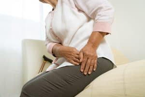 aged woman waking up with hip pain at night