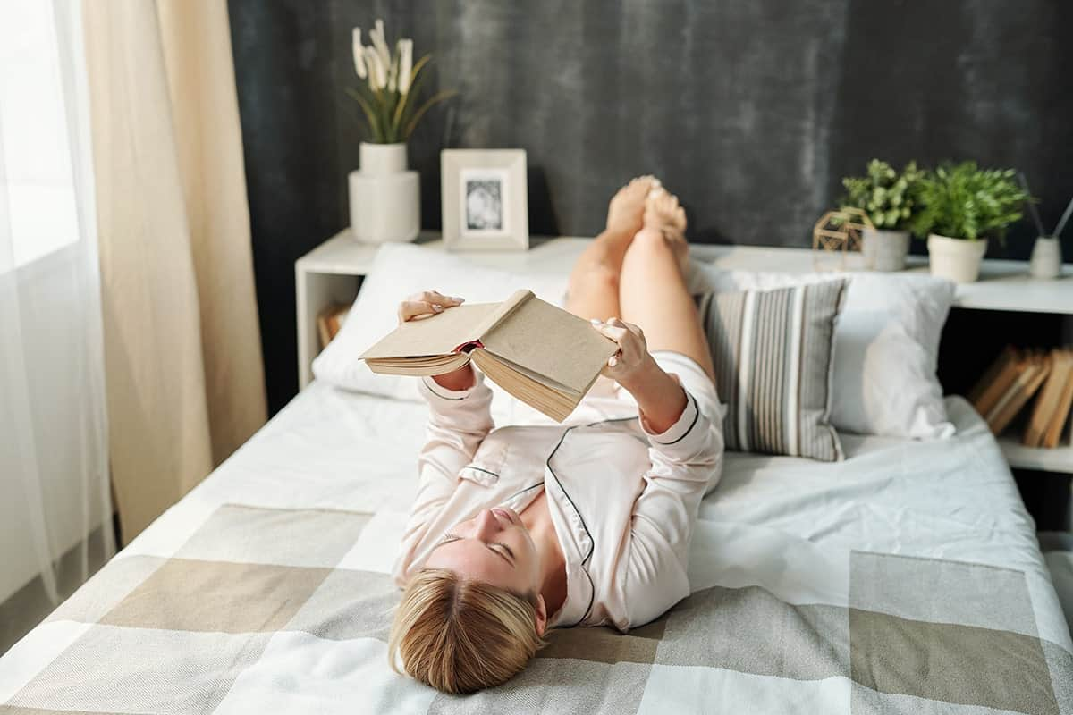 girl reading book in bed lying on back