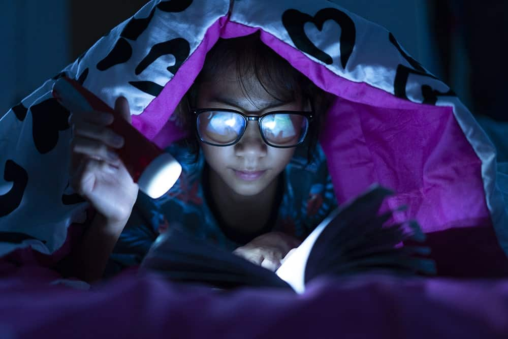 girl reading with book light